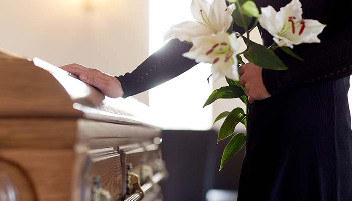woman stood by coffin at funeral service