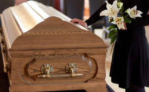 woman stood next to a coffin