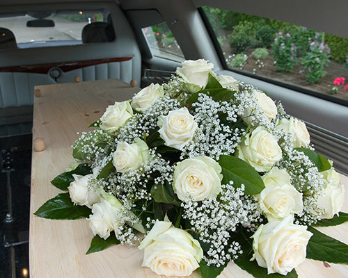 coffin with floral display in back of Swindon Hearse