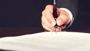Male hand signing papers with fountain pen for Swindon Funeral