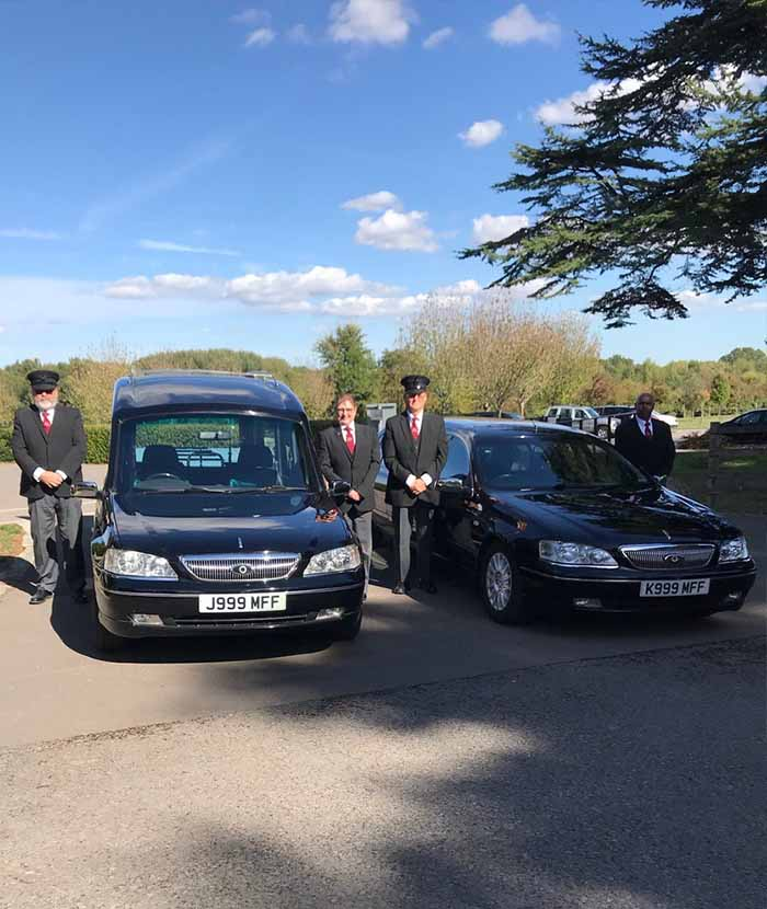 Jem and Karen of Mead Family Funerals stood next to the funeral fleet vehicles-min