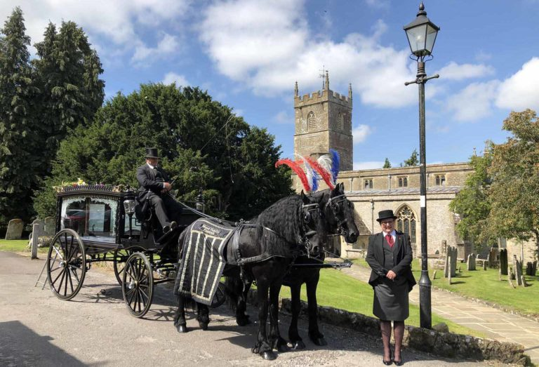 mead faily funerals horse drawn cart and funeral directors outside a church