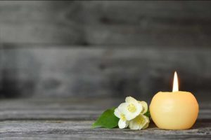 yellow flowers next to a candle